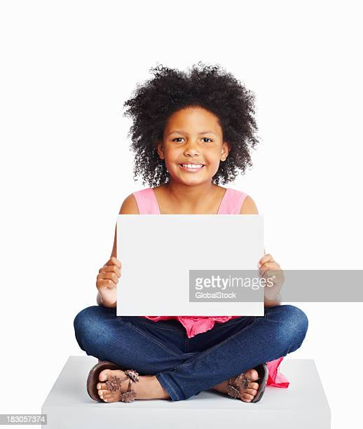 African kid sitting on cube as she holds a billboard