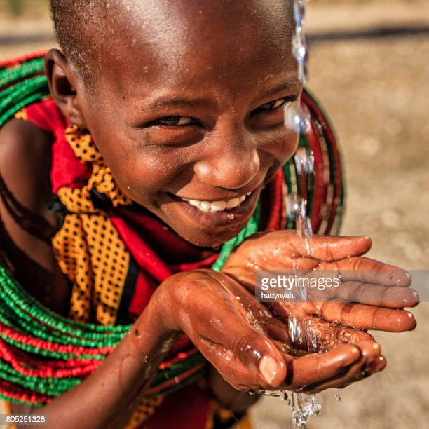 African little girl from Samburu tribe drinking fresh water on savanna., East Africa