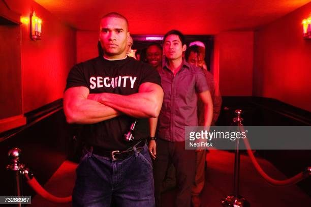 African male bouncer with arms crossed in front of line of people