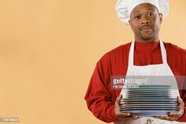 African male chef holding stack of plates