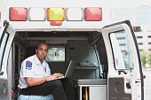 African male EMT using laptop in back of ambulance