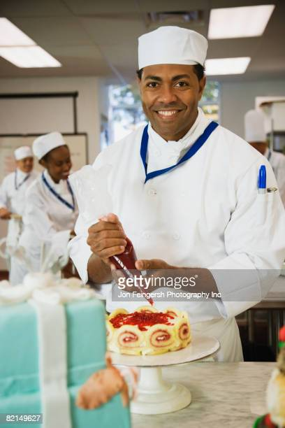 African male pastry chef decorating cake