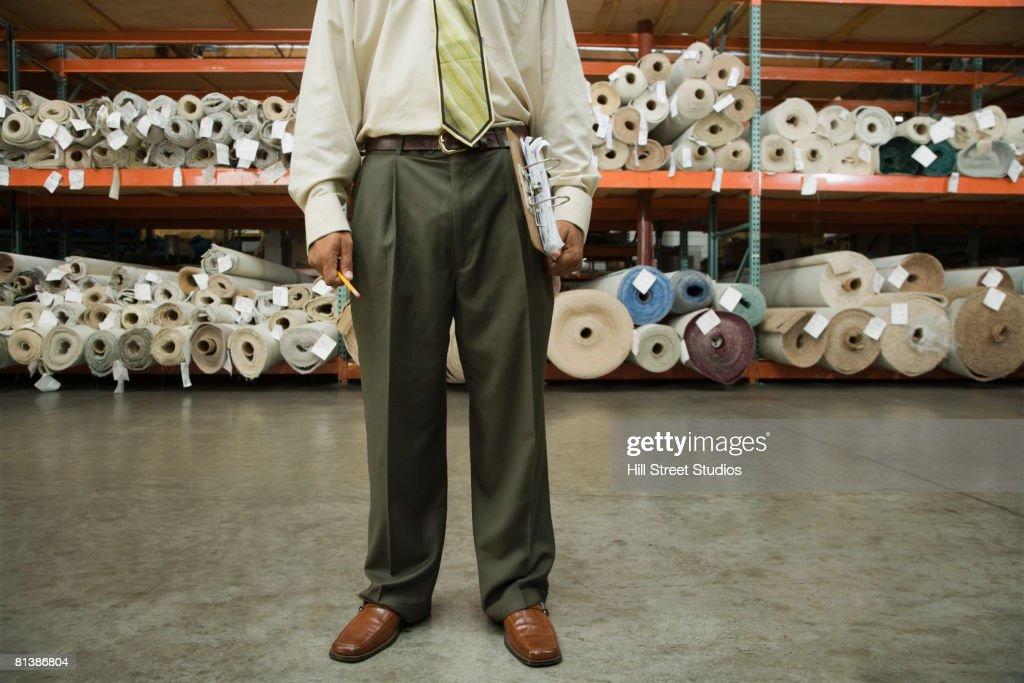 African male sales clerk in flooring warehouse : Stock Photo