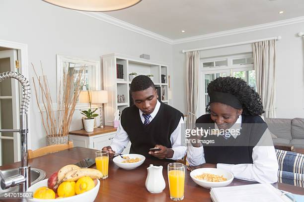 African male student eating breakfast cereal and texting on mobile phone as sister eats cereal, Cape Town, South Africa