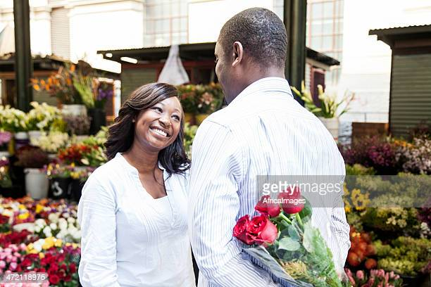 African male surprising his girlfriend with flowers