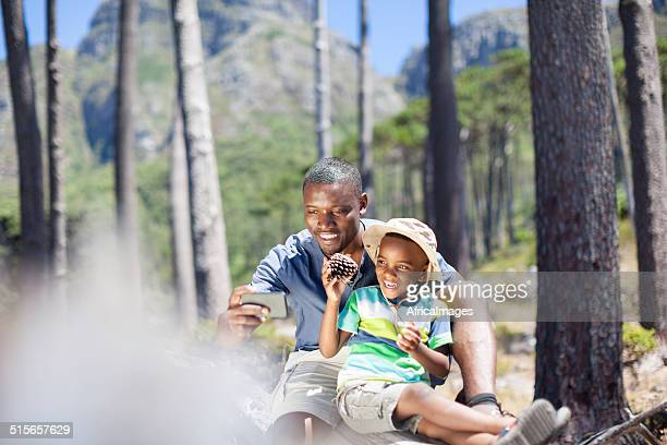 African male taking pictures with his son.