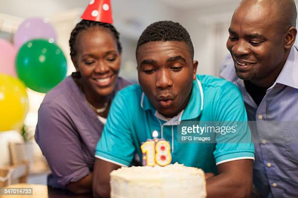 African male teenager blowing out the candles on his 18th birthday cake surrounded by his family , Cape Town, South Africa