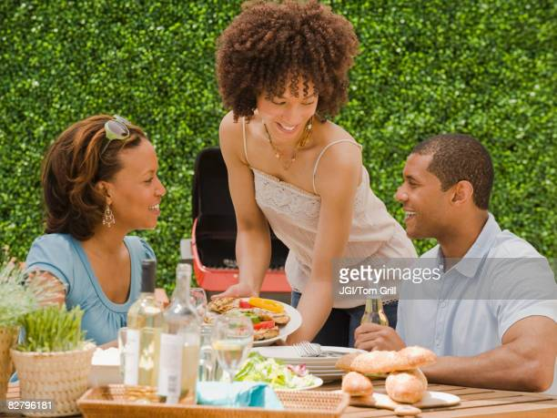 African man and women eating on patio
