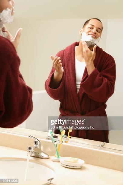 African man applying shaving cream to face