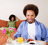 African man carrying breakfast in bed tray