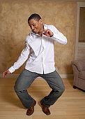 African man dancing in living room