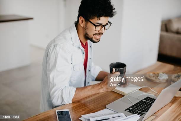 Afrikanischer Mann Kaffee trinken und Surfen Internet auf seinem laptop