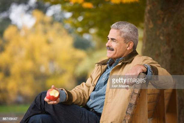 African man eating apple on park bench
