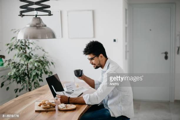 Afrikanischer Mann frühstücken und gehen durch Finanzen