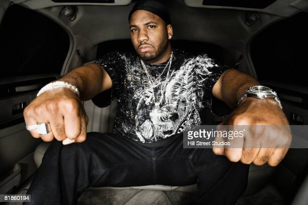 African man holding out fists in limousine