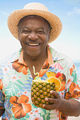 African man holding pineapple drink