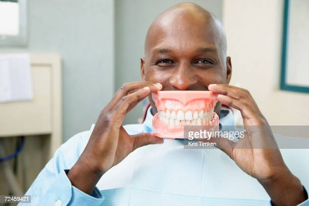 African man in dentist's chair holding up model of teeth