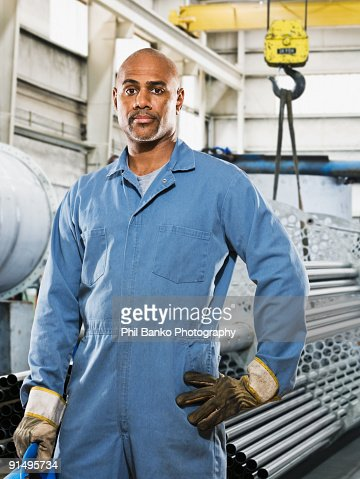 African man in gloves and coveralls in factory