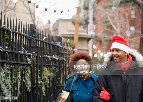African man in santa hat walking outdoors with girlfriend : Stock-Foto