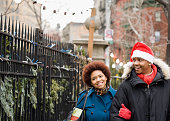 African man in santa hat walking outdoors with girlfriend