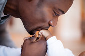 African man kissing his baby in admiration, Cape Town, South Africa.