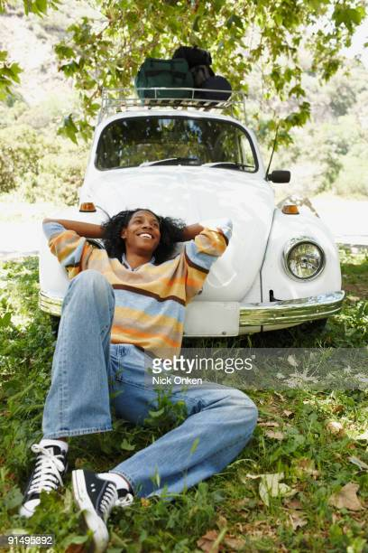 African man laying on hood of car