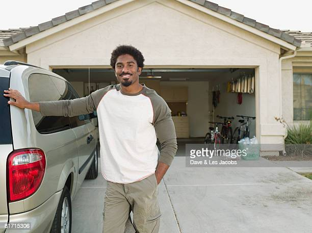 African man leaning on car