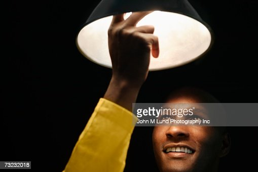 African man looking up and touching light bulb : Foto de stock