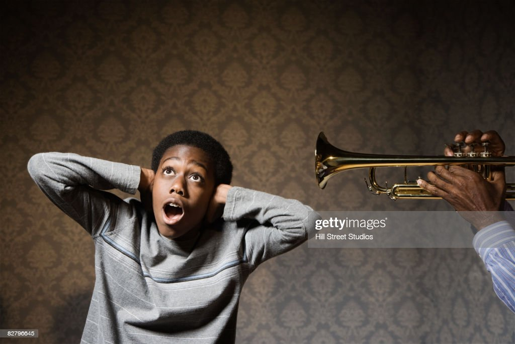 African man playing trumpet in boy's ear