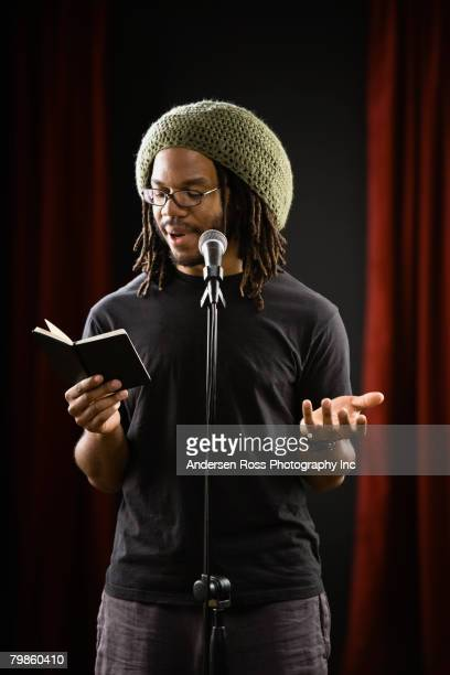 African man reading into microphone