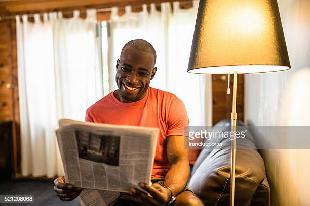 African man reading the newspaper on the living room