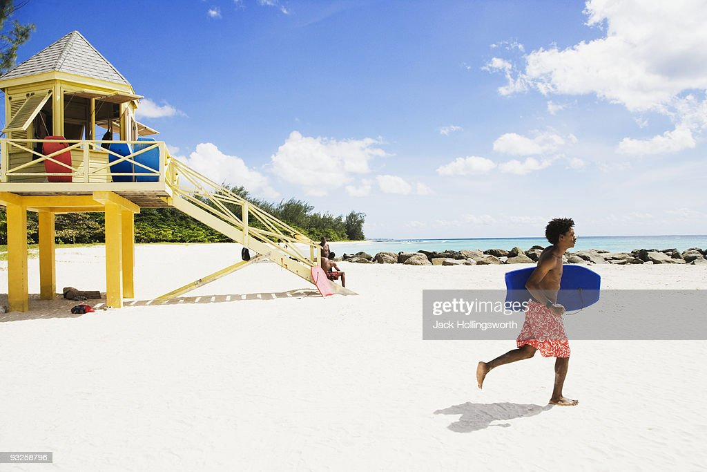 African man running with body board on beach : Stock Photo