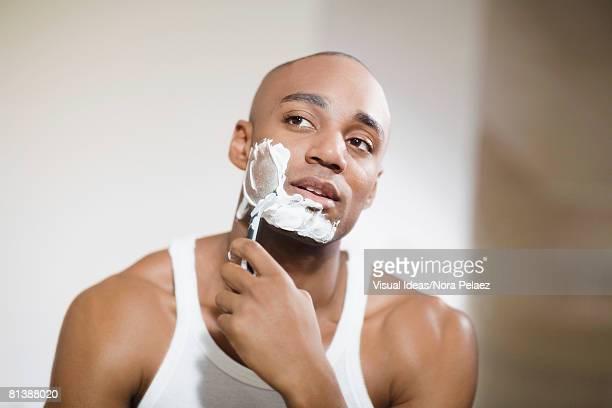 African man shaving face