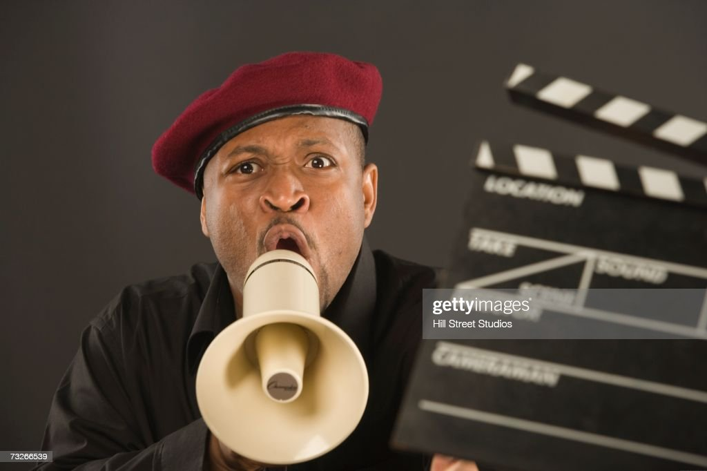 African man shouting in megaphone with clapperboard