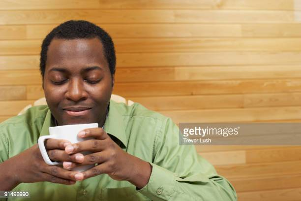 African man smelling cup of coffee