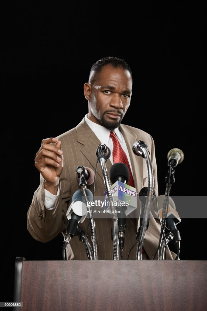African man standing at podium with microphones : Stock Photo