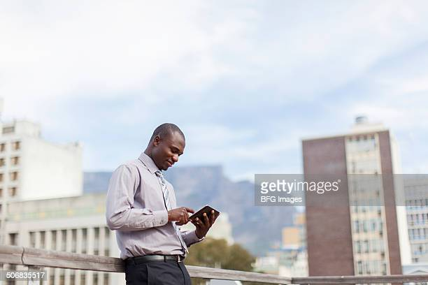 African man standing on rooftop working on digital tablet, Cape Town, South Africa