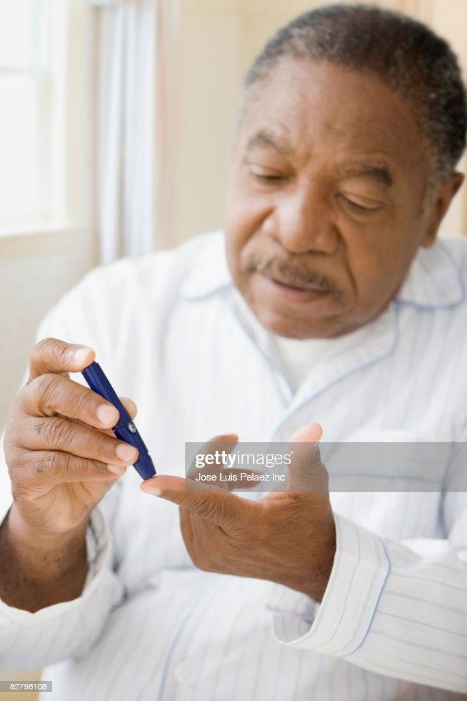 African man using diabetes testing strip : Stock Photo