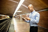 African man using digital tablet while waiting for subway