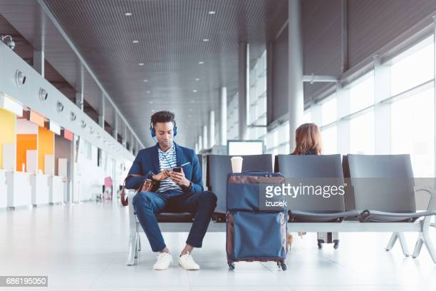 African man waiting for his flight at the airport lounge