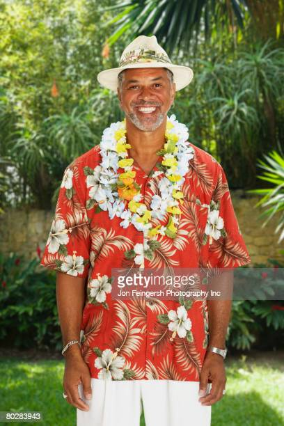 African man wearing Hawaiian shirt and leis