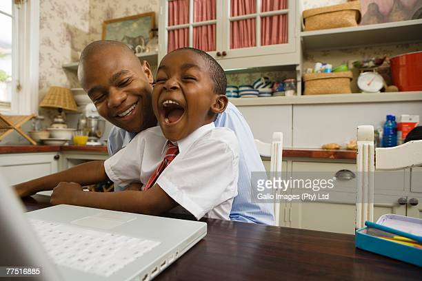 African Man with his Son Using a Laptop