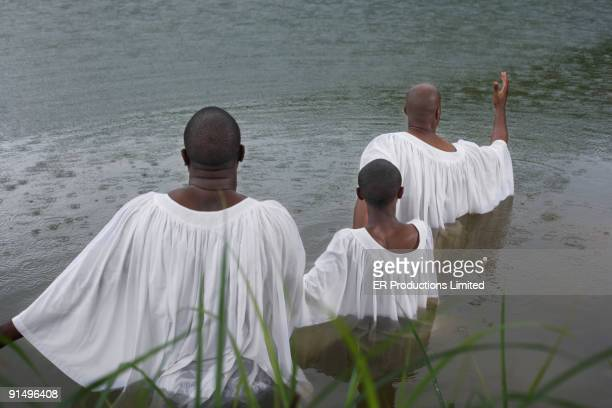 African men and boy getting baptized in lake