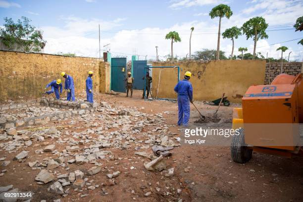 African men are building a wall in the rehabilitation center for former fighters of the AlShabaab militia There are two guards at the gate on May 01...
