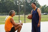 African men talking on basketball court
