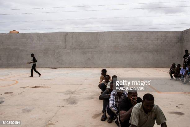 TOPSHOT African migrants have their lunch break in the courtyard of Libya's Karareem detention centre near Misrata a town halfway between Sirte and...