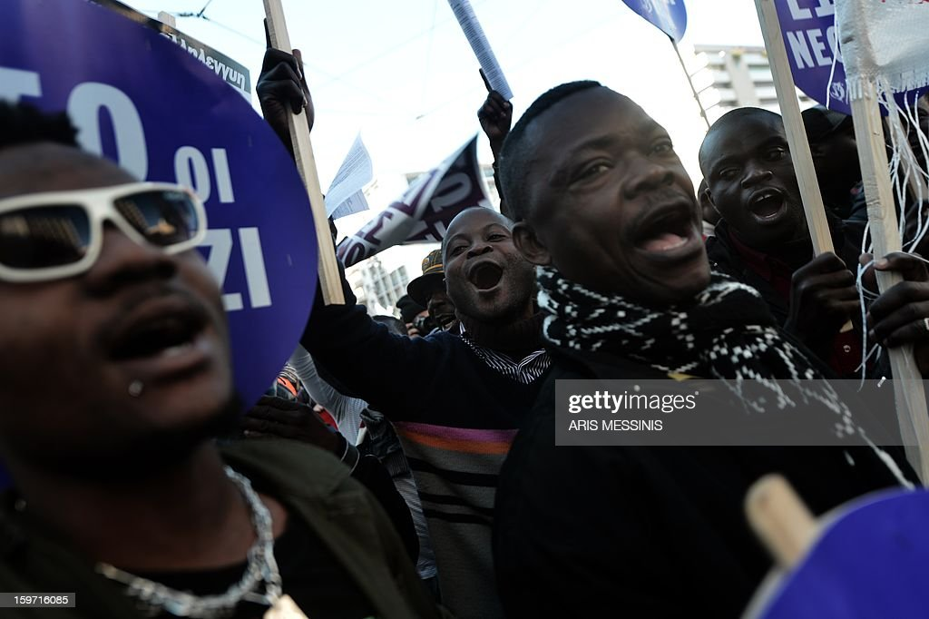 African migrants shout anti-racist slogans on January 19 in Athens as hundreds of Greeks and other nationals marched peacefully against racism and fascism. Nearly 3,000 people joined the rally that was set up by municipalities, organisations, migrant communities and main opposition party radical leftists Syriza. This week, authorities arrested a 29-year-old firefighter and another Greek man aged 25 for the murder of a 27-year-old Pakistani migrant in Athens. MESSINIS
