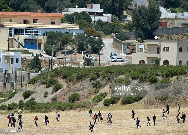 African migrants who were squatting in apartments in the AlIrfane district in Tangier run in a field as they escape Moroccan immigration officers on...