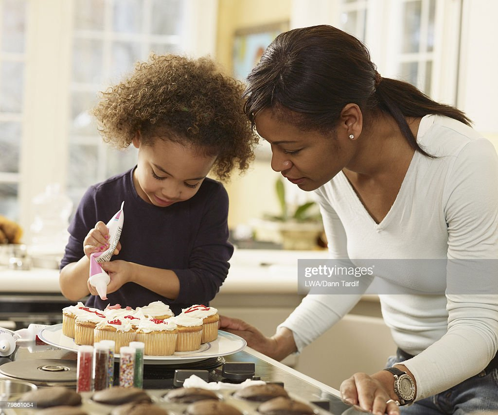 African mother and daughter decorating cupcakes