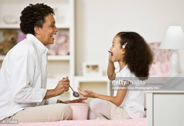 African mother and daughter eating ice cream